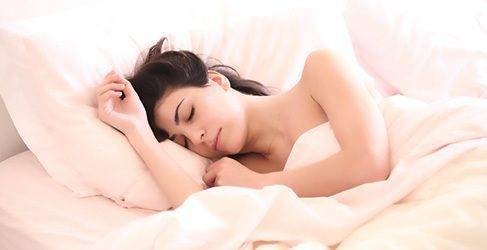 Eine Frau streckt sich nach erholsamem Schlaf